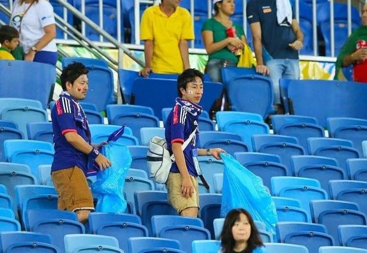 Japanese fans clean up their section f the stand after the game